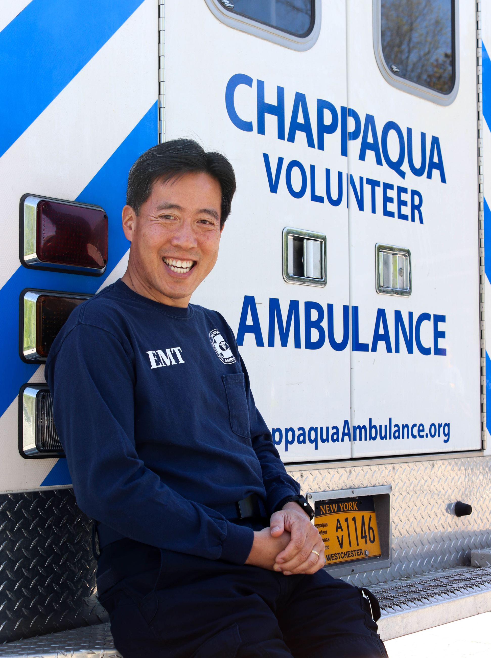 Chappaqua Volunteer Ambulance Member in front of Ambulance